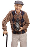 Aîné heureux avec un appareil-photo de vintage et une canne de marche Photographie stock