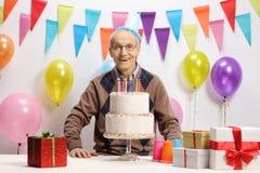 Aîné heureux avec un gâteau d'anniversaire Photo stock