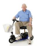 Aîné heureux sur son scooter Image libre de droits