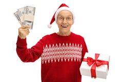 Aîné heureux tenant un cadeau de Noël et des paquets d'argent Photos stock