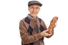 Aîné heureux tenant un sandwich Photographie stock libre de droits