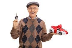 Aîné heureux tenant une clé de voiture et une voiture modèle Images libres de droits