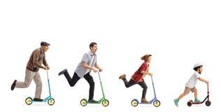 Aîné, homme, jeune homme et scooters d'une équitation d'enfant Photos libres de droits