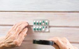 Aîné inspectant des pilules avec la loupe Image stock