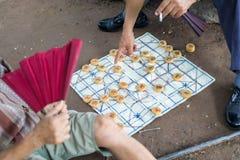 Aîné jouant des échecs chinois au sol Image stock