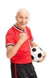 Aîné joyeux avec le poing saisi tenant un football Photographie stock libre de droits