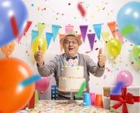 Aîné joyeux avec un gâteau d'anniversaire Image libre de droits