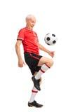 Aîné joyeux jonglant un football et un sourire Image libre de droits