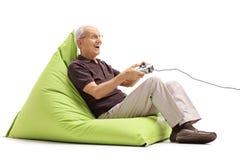 Aîné joyeux jouant des jeux vidéo Photographie stock