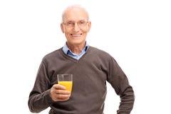 Aîné joyeux tenant un jus d'orange frais Image libre de droits