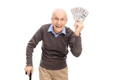 Aîné joyeux tenant une pile d'argent Photographie stock libre de droits