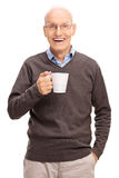 Aîné joyeux tenant une tasse de café blanc Image stock