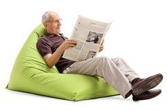 Aîné lisant les actualités posées sur le sac à haricots Images stock