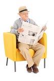 Aîné lisant un journal dans un fauteuil moderne Photos stock
