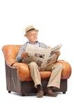 Aîné lisant un journal posé sur le fauteuil Image libre de droits
