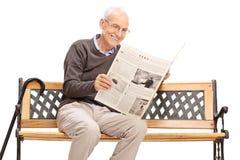 Aîné lisant un journal posé sur un banc Image libre de droits