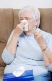 Aîné malade avec le thermomètre soufflant son nez Photo libre de droits
