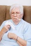 Aîné malade prenant sa température Image stock