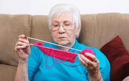 Aîné mettant loin son tricotage Image stock
