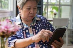Aîné plus âgé vérifiant le social et les actualités de mode de vie avec l'APP dans le MOIS Photo stock