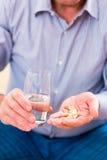 Aîné prenant des pilules d'overdoses à la maison Image libre de droits