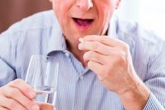 Aîné prenant des pilules d'overdoses à la maison Photographie stock