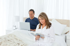 Aîné regardant son PC tandis que son épouse s'affiche Image libre de droits