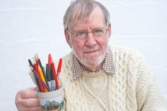 Aîné retenant une tasse de crayons lecteurs et de crayons. Photos stock