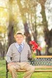 Aîné romantique tenant un groupe de fleurs en parc Photos stock