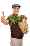 Aîné satisfaisant tenant un sac d'épicerie Photos libres de droits