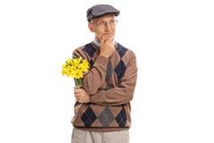 Aîné songeur tenant un groupe de fleurs Image stock