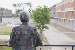 Aîné supérieur se tenant sur le balcon regardant la vue de ville, aîné Images stock