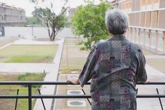 Aîné supérieur se tenant sur le balcon regardant la vue de ville, aîné Photo libre de droits