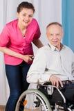 Aîné sur le fauteuil roulant et l'infirmière Photo libre de droits