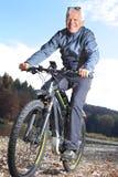 Aîné sur le vélo d'e-montagne près d'une rivière Images libres de droits
