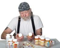 Aîné tenant des bouteilles de prescription avec des pilules sur la table Images libres de droits