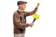 Aîné tenant des fleurs et frappant sur une porte Images stock
