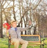 Aîné tenant des fleurs et prenant le selfie en parc Photos libres de droits