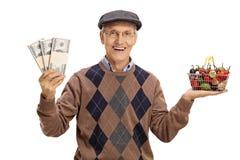 Aîné tenant le petits panier à provisions et argent Photographie stock
