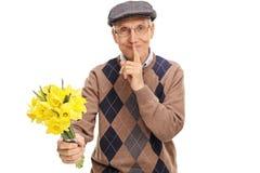 Aîné tenant les fleurs et le doigt sur des lèvres Photographie stock libre de droits