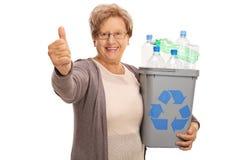 Aîné tenant un bac de recyclage et renonçant au pouce Photo libre de droits