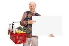 Aîné tenant un panier à provisions et un panneau Photo libre de droits