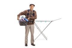 Aîné tenant un panier de blanchisserie devant un drye de support d'habillement photos stock