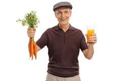 Aîné tenant un verre de jus et de carottes Image stock