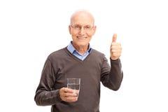 Aîné tenant un verre de l'eau et renonçant à un pouce Photos libres de droits