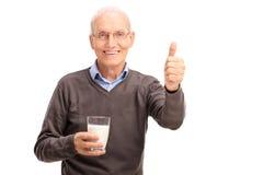 Aîné tenant un verre de lait et renonçant au pouce Photo stock