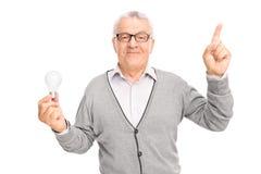Aîné tenant une ampoule et se dirigeant avec son doigt Photo libre de droits