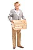 Aîné tenant une caisse en bois vide Photographie stock