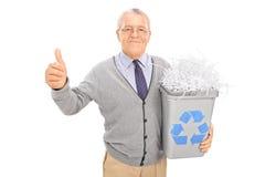 Aîné tenant une poubelle de réutilisation et renonçant au pouce Photo stock
