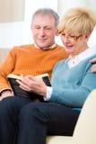 Aînés à la maison lisant un livre ensemble Image libre de droits